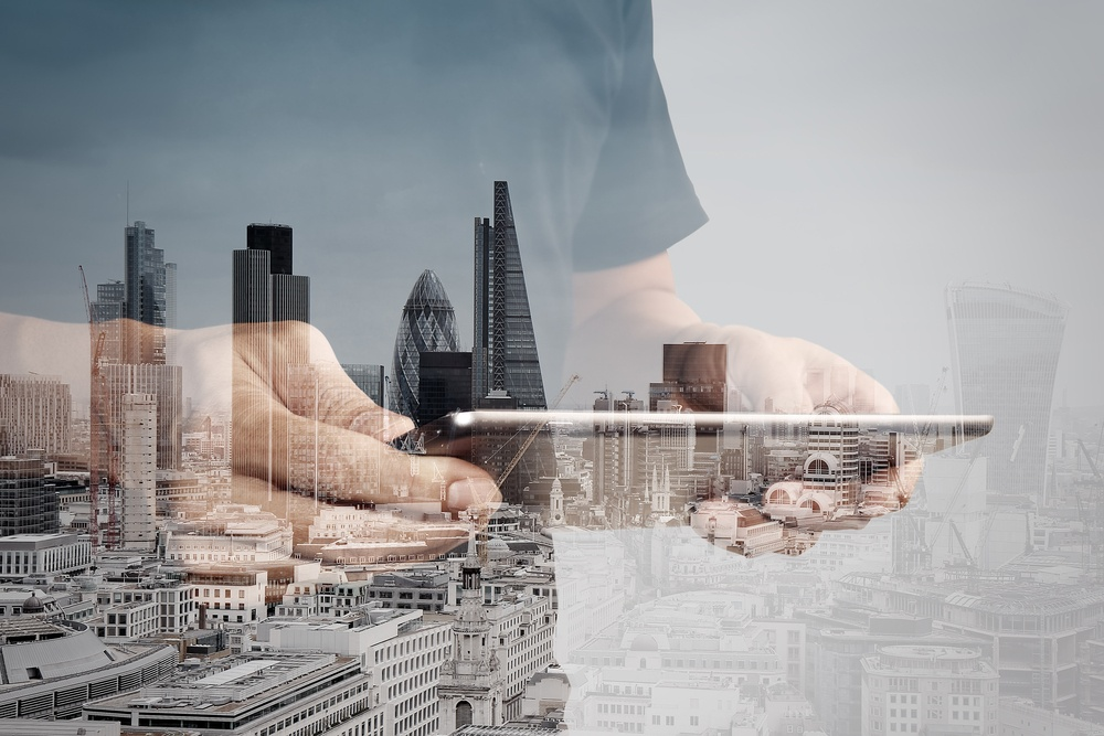 Double exposure of success businessman using digital tablet with london building and social media diagram .jpeg